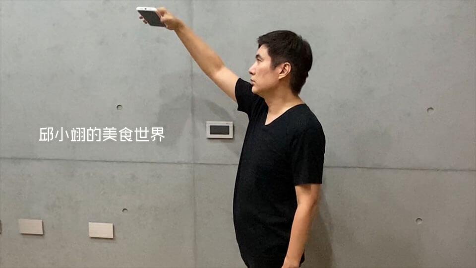 右手拿着iPhone之后,将手举高,约莫高出头顶旳位置
